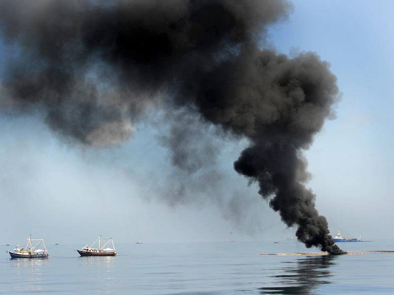 Two fishing vessels drag an oil boom