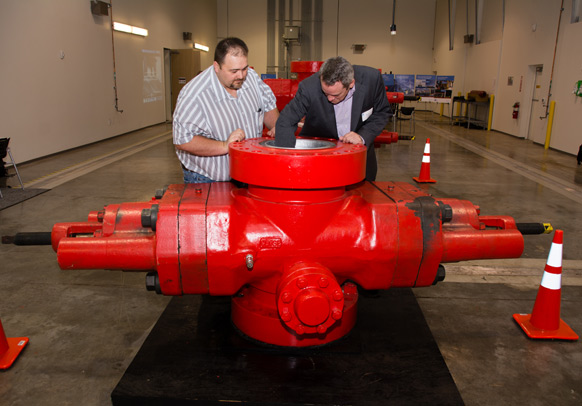 Attendees of the Lloyd's Register Training Center Open House look into the Blowout Preventer in the workshop.