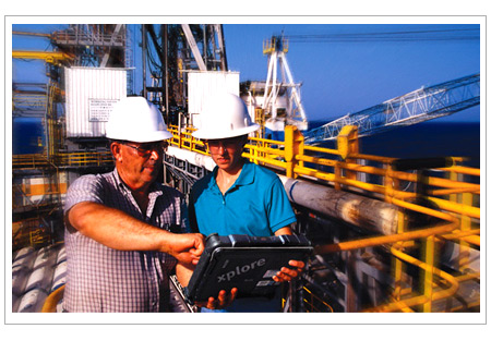 Oil Rig workers on rig with tablet computer